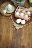 Organische rohe Hühnereien im Eikasten auf hölzernem Hintergrund Stockbild