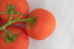 Organische rote Tomaten auf einer Draufsicht des Marmorschneidebretts Lizenzfreie Stockbilder