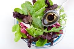 Organische salade en lepel van olijfolie stock foto's