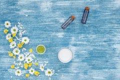 Organische schoonheidsmiddelen met kamille op blauwe hoogste mening als achtergrond stock afbeeldingen