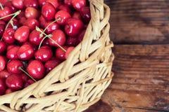 organische selbstgezogene Kirschen in einem Korb, auf hölzernem Hintergrund stockfotos