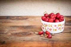organische selbstgezogene Kirschen und Steine in einer keramischen Schüssel der Weinlese, auf hölzernem Hintergrund stockfoto