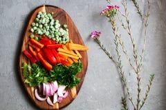 Organische vegetarische ingrediënten voor een salade met sla, paprika en bevroren erwten op rustieke houten scherpe raad stock foto