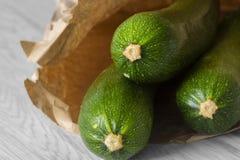 Organische Zucchini in einer braunen Papiert?te Recycle Verpackenkonzept Kein Kunststoffabfall stockfotos