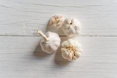 Organischer Knoblauch ganz und Nelken auf weißem hölzernem Hintergrund stockbilder