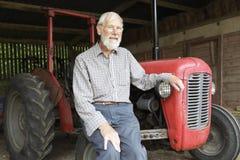 Organischer Landwirt, der durch Vintage Tractor sitzt Stockbilder