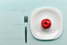 Organischer roter Apfel auf einer Platte Lizenzfreie Stockbilder