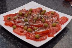 Organischer Tomatensalat auf einer weißen Platte Stockfotografie
