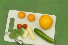 Organisches Gemüse und Frucht auf weißem Schneidebrett Stockbild