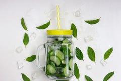 Organisches Limonadengetränk des neuen Sommers mit Scheiben Gurke, Eis, Minze, in einem Glasgefäß mit einem gelben Deckel und ein lizenzfreies stockbild
