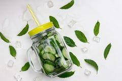 Organisches Limonadengetränk des neuen Sommers mit Scheiben Gurke, Eis, Minze, in einem Glasgefäß mit einem gelben Deckel und ein stockfotos
