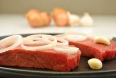 organisches Steak mit Zwiebel in einer Wanne Stockbild