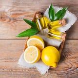 Organisches wesentliches Zitronenöl mit Grünblättern und -frucht stockfotos
