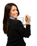 Organised businesswoman. Pretty brunette in formal business attire records her schedule in her organiser Stock Photos
