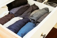 Organised wardrobe, rolling shirts is the trick. Clever sectioning and rolling your shirts is a clever hack for organisation stock images