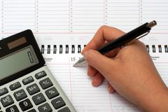 Organiser entry. Calculator, organizer and pen in hand starting to write Royalty Free Stock Image