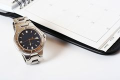 Organiser Watch. A watch placed next to an organiser royalty free stock photography