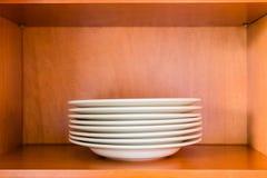 Organisierter minimalistic Küchenschrank mit einem Stapel weißem por Stockfoto
