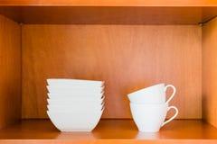 Organisierter minimalistic Küchenschrank mit weißer Porzellanschüssel Lizenzfreies Stockfoto