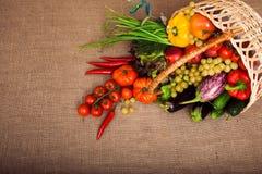 Organisk grönsaker, frukter och grönsallat i vide- korg på kitch Royaltyfria Bilder