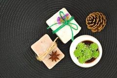 Organisk handgjord tvålgarnering vid pinecone, torkar blommor, stjärnaanis och den suckulenta växten på svart mattt Royaltyfria Bilder