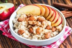 Organisk havremjölhavregröt i den vita keramiska bunken med äpplet, mandeln, honung och kanel sund frukost Royaltyfri Foto