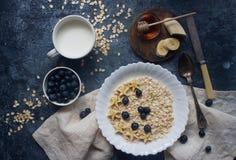 Organisk havremjölhavregröt med blåbäret, bananen, honung och mjölkar på den mörka stentabellen, sund livsstil och bantar begrepp Fotografering för Bildbyråer