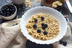 Organisk havremjölhavregröt med blåbäret, bananen, honung och mjölkar på den mörka stentabellen, sund livsstil och bantar begrepp Arkivbild