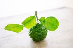 Organisk kaffirlimefrukt på träbakgrund Royaltyfri Foto