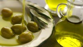 Organisk olivolja som häller till oliv stock video