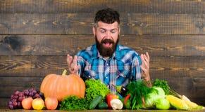 Organisk skördbonde för grönsaker som är chockad på grund av ljusa grönsaker Lantbruk- och plockningbegrepp Uppsökt man royaltyfri fotografi