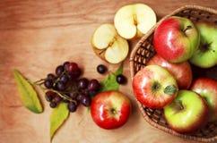 Organiska äpplen i en korg på en trätabell Arkivbild