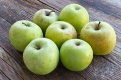 Organiska äpplen på träbakgrund royaltyfria foton