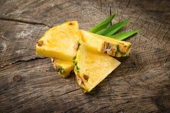 Organiska ananasskivor på träbakgrund arkivbild