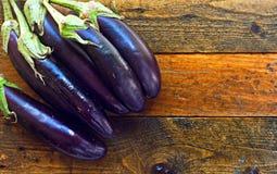 Organiska aubergines på lantligt trä bordlägger Royaltyfria Foton