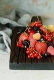 Organiska bär på ett träbräde Ljus efterrätt för sommar av bär på en grå bakgrund sund mat Sommar och sund mat lurar Royaltyfri Bild