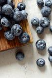 Organiska blåbärbär på ett träbräde Ljus efterrätt för sommar av bär på en grå bakgrund sund mat Sommar och hälsa Royaltyfri Foto