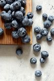 Organiska blåbärbär på ett träbräde Ljus efterrätt för sommar av bär på en grå bakgrund sund mat Sommar och hälsa Royaltyfria Foton