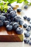 Organiska blåbärbär på ett träbräde Ljus efterrätt för sommar av bär på en grå bakgrund sund mat Sommar och hälsa Fotografering för Bildbyråer