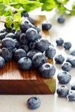 Organiska blåbärbär på ett träbräde Ljus efterrätt för sommar av bär på en grå bakgrund sund mat Sommar och hälsa Arkivfoto
