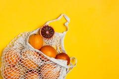 Organiska blodiga apelsiner i den återvinningsbara påsen för bomullsingrepp, gul bakgrund - återanvända, hållbar livsstil, nollav arkivfoton
