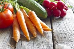 Organiska grönsaker för ny vår på träbräde Arkivbild