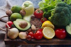 Organiska grönsaker, frukt, muttrar, frö och örter i träask i lantlig stil Arkivfoton