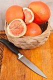 Organiska grapefrukter i en korg och en kniv Royaltyfri Foto
