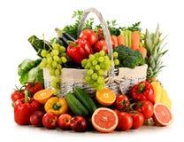 Organiska grönsaker och frukter i vide- korg på vit Royaltyfria Foton