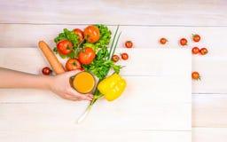 Organiska ingredienser för närbild på en träbakgrund Artistiska olika grönsaker En hand som rymmer ett exponeringsglas fullt av o Royaltyfri Fotografi