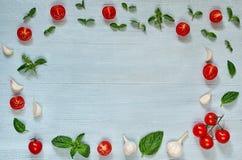 Organiska ingredienser för sallad: skivade körsbärsröda tomater, nya basilikasidor, vitlök på den gråa bakgrunden med kopieringsu royaltyfri fotografi