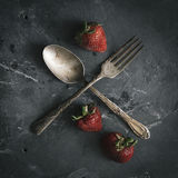 Organiska jordgubbar som är ordnade med bestick Royaltyfri Bild