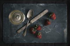 Organiska jordgubbar som är ordnade med bestick Arkivfoto