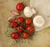 Organiska körsbärsröda tomater, champinjoner, vitlök och örtar på en gammal lantlig stenskärbräda Royaltyfria Foton